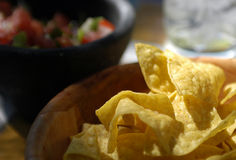 Mexican food - Chips & salsa. A bowl of tortilla chips on the table of a neighborhood mexican restaurant with salsa and a glass of water visible behind Stock Photography