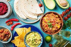 Mexican food mix. Nachos, fajitas, tortilla, guacamole and salsa sauces and ingredients over blue background. Top view Stock Photography