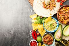 Mexican food mix. Nachos, fajitas, tortilla, guacamole and salsa sauces and ingredients over black background. Top view with copy space Stock Photography