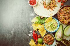 Mexican food mix. Nachos, fajitas, tortilla, guacamole and salsa sauces and ingredients over black background. Top view with copy space Royalty Free Stock Photography