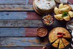 Mexican food mix - tacos, cornbread, salsa with tomato, red onion, lime, cilantro, corn and hot pepper sauce, empanadas. Copy spac. E Stock Photos