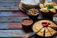 Mexican food mix - tacos, cornbread, salsa with tomato, red onion, lime, cilantro, corn and hot pepper sauce, empanadas. Copy spac. E Royalty Free Stock Images