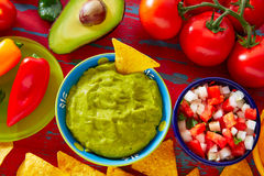 Mexican food nachos guacamole pico gallo cheese. Mexican food nachos guacamole pico de gallo and chili peppers sauces royalty free stock photo
