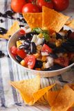 Mexican Food: salsa with black beans and nachos closeup. Vertica Royalty Free Stock Photo