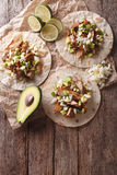 Mexican food: tortilla with carnitas, onions and avocado. Vertical top view. Mexican food: tortilla with carnitas, onions and avocado close-up on the table royalty free stock photos