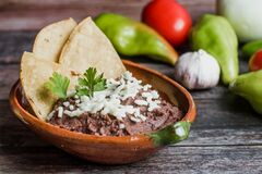 Free Mexican Fried Beans Called Frijoles Refritos, Plate Of Black Beans On A Wooden Table In Mexico Stock Image - 193513811