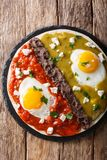 Mexican fried huevos divorciados eggs with salsa verde and roja, cheese, black beans on a tortilla close-up. Vertical top view. Mexican fried huevos divorciados royalty free stock image