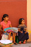 Mexican girls selling textiles. Little girls selling traditional clothes in the street (Oaxaca, Mexico Royalty Free Stock Images