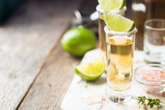 Mexican Gold Tequila. Shots with lime and salt on wooden table over black background Royalty Free Stock Photography