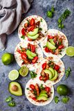 Mexican grilled chicken tacos with avocado, tomato, onion on rustic stone table. Recipe for Cinco de Mayo party. stock image