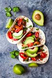 Mexican grilled chicken tacos with avocado, tomato, onion on rustic stone table. Recipe for Cinco de Mayo party. stock photography