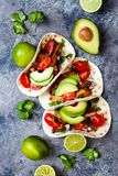 Mexican grilled chicken tacos with avocado, tomato, onion on rustic stone table. Recipe for Cinco de Mayo party. royalty free stock image