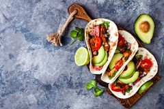Mexican grilled chicken tacos with avocado, tomato, onion on rustic stone table. Recipe for Cinco de Mayo party. Top view, overhead, flat lay stock image