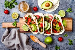 Mexican grilled chicken tacos with avocado, tomato, onion on rustic stone table. Recipe for Cinco de Mayo party. Top view, overhead, flat lay stock photography