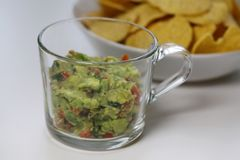 Guacamole with a Bowl of Nachos. Mexican guacamole with corn nachos. The guacamole is homemade, fresh and delicious and it`s in the foreground of this photo royalty free stock image