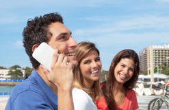 Mexican guy laughing at phone with girlfriends in the background. Attractive mexican guy laughing at phone with happy girlfriends in the background outside in Royalty Free Stock Photos