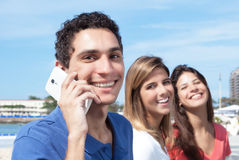 Mexican guy talking at phone with two girlfriends in the background Royalty Free Stock Photos