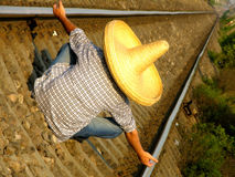 Mexican guy waiting the train. Mexican man with a sombrero sitting on the train rail Royalty Free Stock Photography