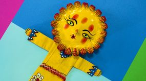 Mexican handicraft, hand painted doll representing the sun. On a colorful paper background Royalty Free Stock Image