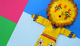 Mexican handicraft, hand painted doll representing the sun. On a colorful paper background Royalty Free Stock Images