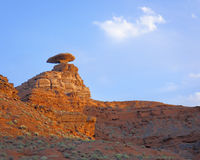 Mexican Hat Landscape. Precariously balanced hat shaped red rock formation beneath bright blue sky with cloud royalty free stock photos