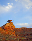 Mexican Hat Portrait. Precariously balanced hat shaped red rock formation beneath bright blue sky with clouds in portrait orientation royalty free stock image