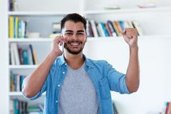Mexican hipster man with beard cheering at phone stock photography