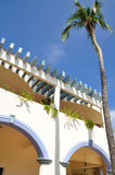 Mexican home and palm tree. Low angle view of traditional Mexican colonial style home with palm tree and blue sky background Royalty Free Stock Photo