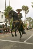 Mexican horseback riders trot along during the opening day parade down State Street of Old Spanish Days Fiesta held every August i Royalty Free Stock Images