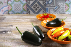 Mexican hot chili peppers colorful mix jalapeno on orange bowls Royalty Free Stock Images