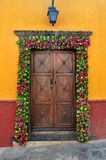 Mexican house Colonial style door with flowers decoration Stock Photography