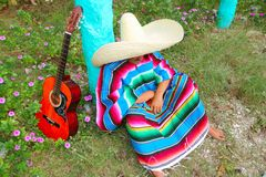 Mexican lazy sombrero hat man poncho nap garden. Mexican lazy sombrero hat man poncho nap in garden typical topic Royalty Free Stock Photography