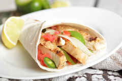 Mexican lunch. Tasty Mexican fast food of fajitas burrito with grilled pork or chicken (white meat Royalty Free Stock Image