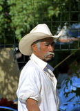 Mexican man close up. Fierce looking senior mexican man in white with sombrero hat and mustache royalty free stock image