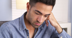Mexican man feeling sad and looking down Stock Photo