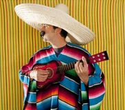 Mexican man serape poncho sombrero playing guitar royalty free stock photo