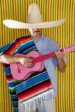 Mexican man serape poncho sombrero playing guitar Stock Image