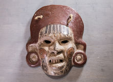 Mexican Mayan Aztec wood and ceramic mask. Women scary face on wood background Royalty Free Stock Images