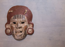Mexican Mayan Aztec wood and ceramic mask. Women scary face on wood background Royalty Free Stock Photography
