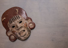 Mexican Mayan Aztec wood and ceramic mask. Women scary face on wood background Royalty Free Stock Photos