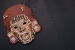 Mexican Mayan Aztec wood and ceramic mask. Women scary face on black background Stock Image