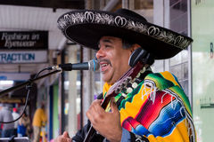 Mexican Musician Busking on the Street. MELBOURNE / AUSTRALIA - SEPTEMBER 5 2015: Hampton Street Fathers Day Car Show - A Mexican Busker playing to a crown Royalty Free Stock Photo