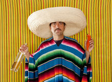 Mexican mustache chili drunk tequila sombrero man. Mexican typical man eating chili hot pepper and drinking tequila with poncho Stock Image