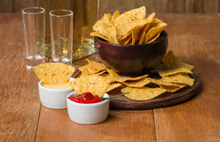 Mexican nacho chips, cheese and salsa dip in bowl and tequila Stock Images