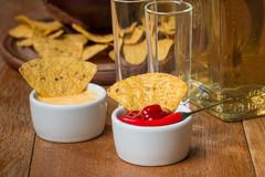 Mexican nacho chips, cheese and salsa dip in bowl and tequila Stock Photos