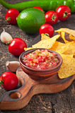 Mexican nacho chips and salsa dip. In bowl on wooden background stock image