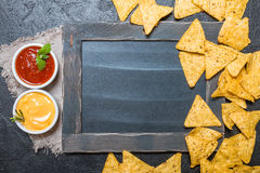 Mexican nacho with sauces and chalk board. On black background, top view, copy space Stock Photo