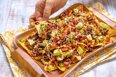 Mexican nacho yellow corn tortilla chips with cheese, meat, avocado guacamole and red salsa Royalty Free Stock Photos