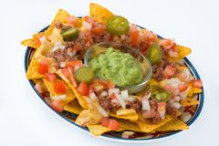 Mexican nachos with beef, guacamole, cheese sauce, peppers, tomato and onion in plate isolated stock photography