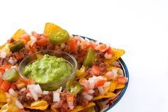 Mexican nachos with beef, guacamole, cheese sauce, peppers, tomato and onion in plate isolated royalty free stock images